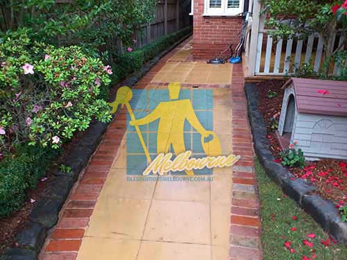 outdoor sandstone tiles pavers wet from cleaning with quarry tiles around